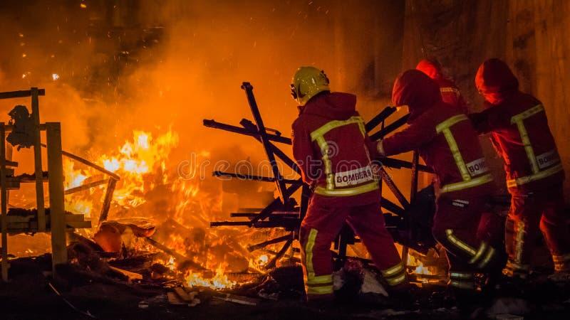 Τα άτομα πυρκαγιάς ωθούν τα υπόλοιπα ενός falla στην πυρκαγιά κατά τη διάρκεια Las Fallas στη Βαλένθια Ισπανία στοκ φωτογραφία