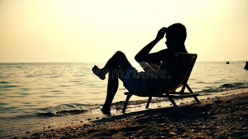 Τα άτομα σκιαγραφιών στην ανάγνωση καρεκλών κρατούν στο ηλιοβασίλεμα παραλιών στοκ εικόνα με δικαίωμα ελεύθερης χρήσης