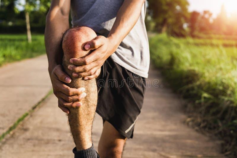 Τα άτομα τραυμάτισαν από τη χρήση άσκησης τα χέρια σας για να κρατήσουν τα γόνατά σας στο πάρκο στοκ εικόνες