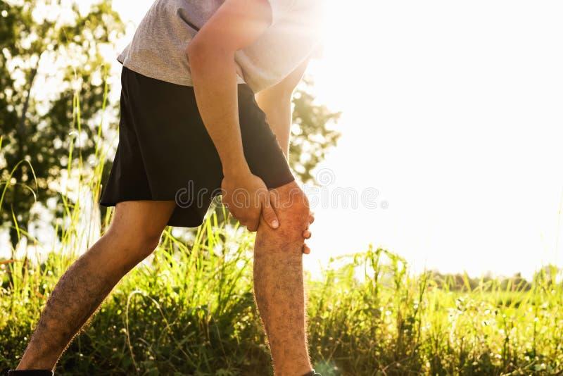 Τα άτομα τραυμάτισαν από τη χρήση άσκησης τα χέρια σας για να κρατήσουν τα γόνατά σας στο πάρκο στοκ φωτογραφίες με δικαίωμα ελεύθερης χρήσης