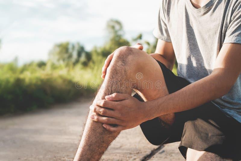 Τα άτομα τραυμάτισαν από τη χρήση άσκησης τα χέρια σας για να κρατήσουν τα γόνατά σας στο πάρκο στοκ εικόνες με δικαίωμα ελεύθερης χρήσης