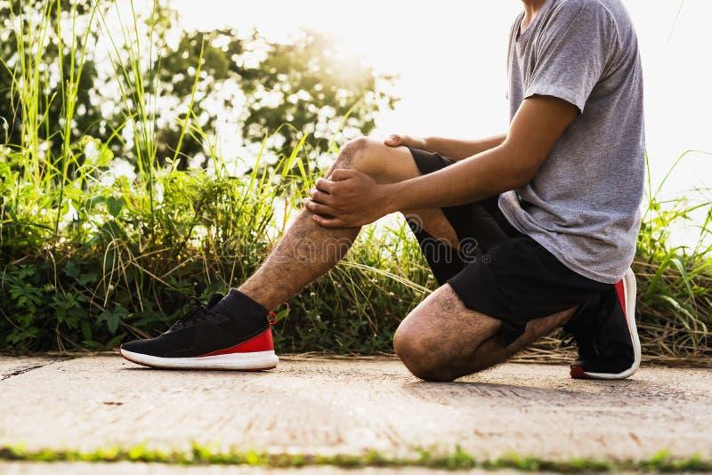 Τα άτομα τραυμάτισαν από τη χρήση άσκησης τα χέρια σας για να κρατήσουν τα γόνατά σας στο πάρκο στοκ εικόνα