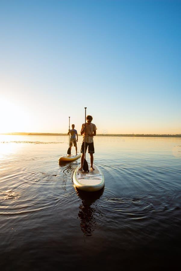 Τα άτομα, φίλοι χαλαρώνουν σε μια ΓΟΥΛΙΑ επιβιβάζονται κατά τη διάρκεια του ηλιοβασιλέματος στοκ φωτογραφίες