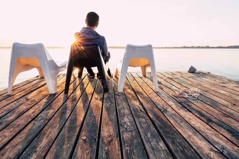 Τα άτομα χαλαρώνουν και περισυλλογή στην καρέκλα στη γέφυρα για πεζούς στη λίμνη στοκ φωτογραφία με δικαίωμα ελεύθερης χρήσης