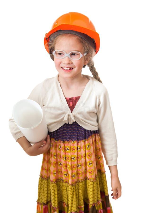Τα έξι έτη χαμογελούν το κορίτσι στις hardhat στάσεις με το ρόλο των σχεδίων στοκ εικόνες