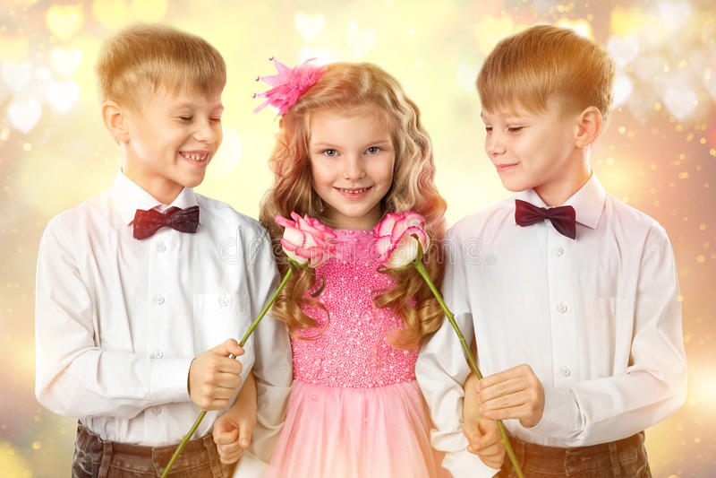 Τα δίδυμα αγόρια δίνουν ένα μικρό κορίτσι λουλουδιών Βαλεντίνος ` s και πορτρέτο τέχνης ημέρας γυναικών Παιδί και αγάπη παιδιών στοκ φωτογραφίες