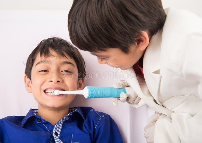 Τα αγόρια διδάσκουν το ένα το άλλο πώς να χρησιμοποιήσουν την ηλεκτρική οδοντόβουρτσα στοκ φωτογραφία με δικαίωμα ελεύθερης χρήσης