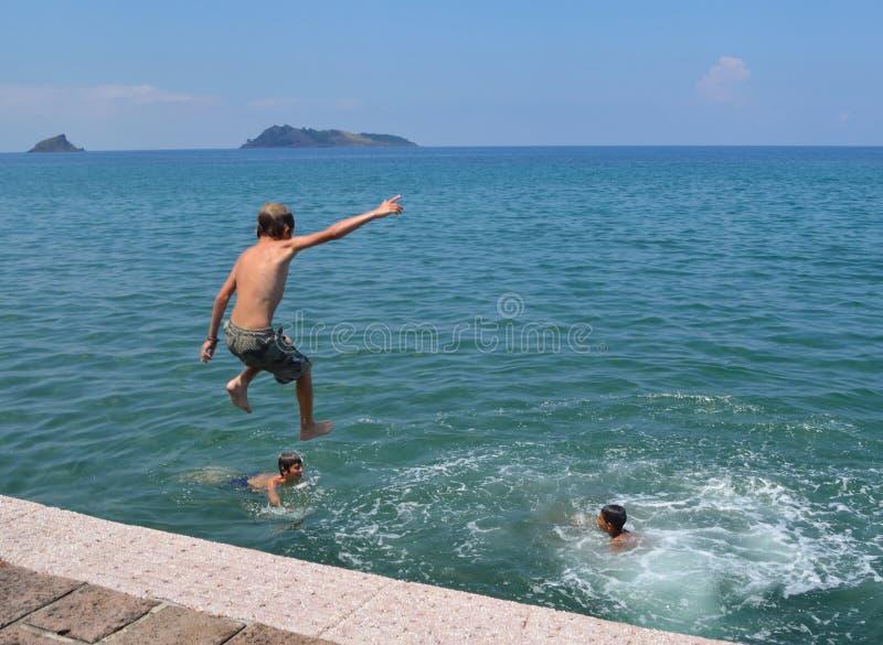 Τα αγόρια πηδούν από το λιμενοβραχίονα στοκ φωτογραφία