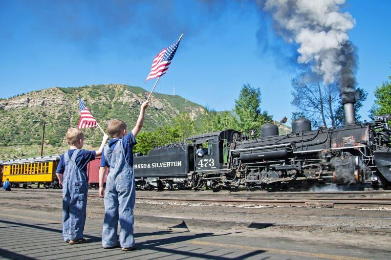 Τα αγόρια στη αμερικανική σημαία κυμάτων φορμών εκπαιδεύουν την αναχώρηση στοκ εικόνα