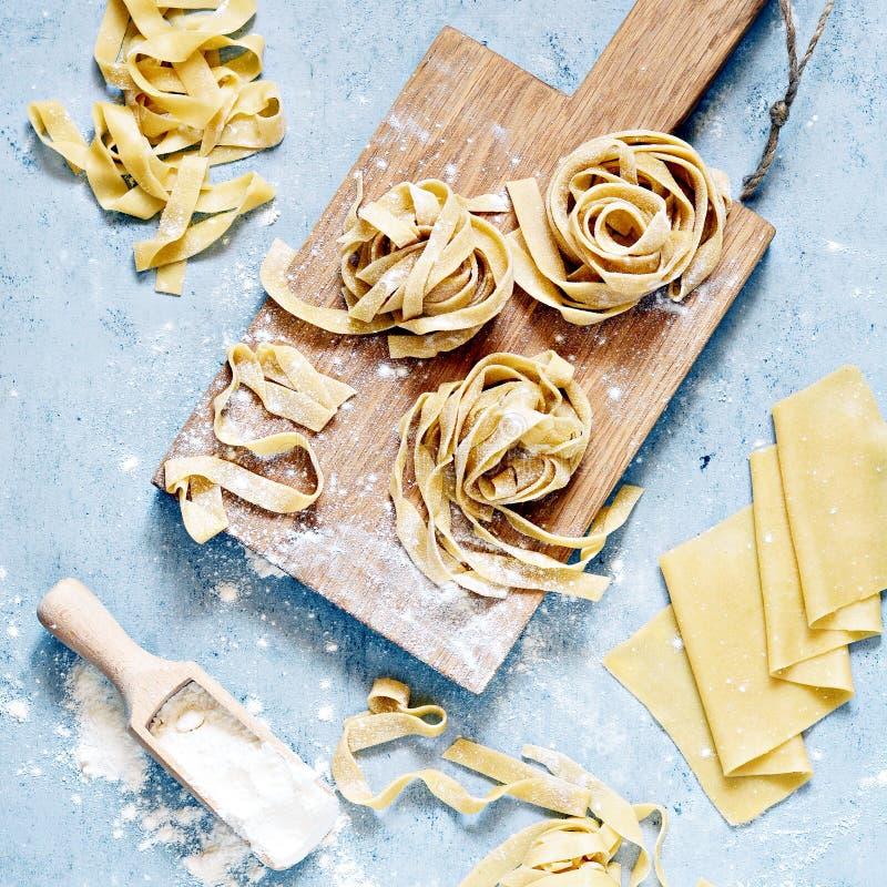 Τα ακατέργαστα κίτρινα ιταλικά ζυμαρικά pappardelle, το fettuccine ή tagliatelle σε ένα μπλε υπόβαθρο, κλείνουν επάνω στοκ εικόνες
