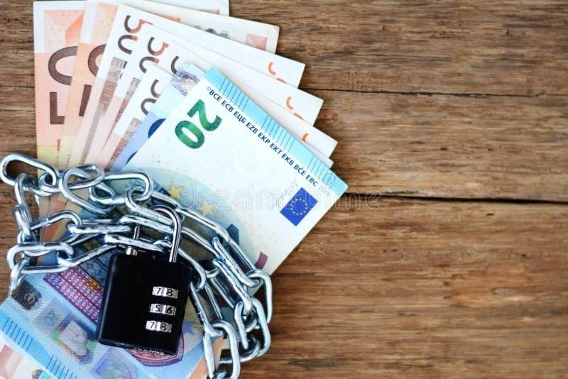 Τα αλυσοδεμένα επάνω χρήματα, εξασφαλίζουν την έννοια αποταμίευσής σας με τα τραπεζογραμμάτια, την αλυσίδα και το λουκέτο μετρητώ στοκ φωτογραφία