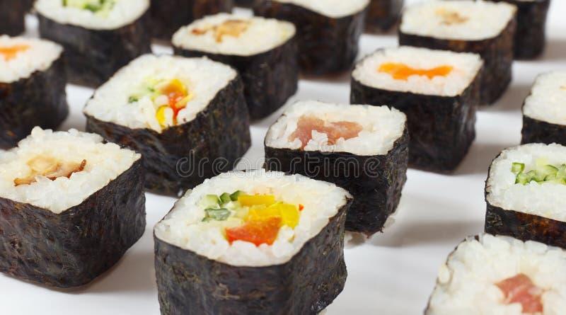 Τα ανάμεικτα ασιατικά σούσια με το σολομό, τον τόνο, το χέλι και τα λαχανικά στο άσπρο υπόβαθρο κλείνουν επάνω στοκ εικόνες