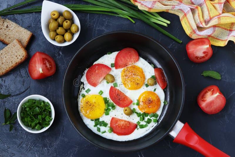 Τα ανακατωμένα αυγά με τις ντομάτες και τα πράσινα κρεμμύδια σε ένα τηγανίζοντας τηγάνι σε ένα σκοτεινό υπόβαθρο, στον πίνακα είν στοκ εικόνα