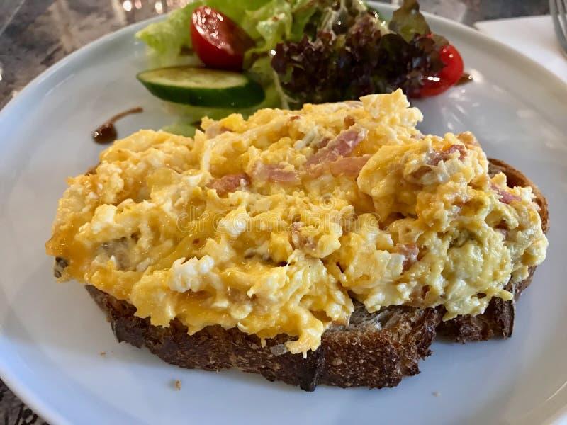 Τα ανακατωμένα αυγά με το ψωμί μαγιάς, τυρί τυριού Cheddar, φέτες μπέϊκον ε στοκ εικόνες