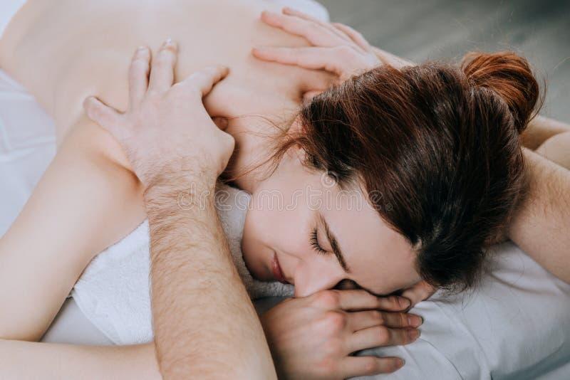 Τα ανθρώπινα χέρια του μασέρ κάνουν τον ώμο μασάζ μιας νέας γυναίκας Όμορφο χαλαρωμένο πρόσωπο μιας νέας γυναίκας στοκ εικόνα με δικαίωμα ελεύθερης χρήσης