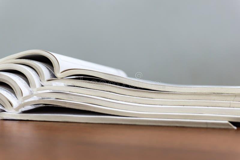 Τα ανοικτά περιοδικά βρίσκονται το ένα πάνω από το άλλο σε έναν καφετή πίνακα, τα έγγραφα είναι συσσωρευμένη κινηματογράφηση σε π στοκ φωτογραφία