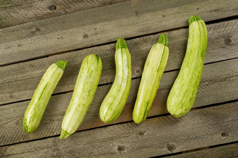 Τα ανοικτό πράσινο φρέσκα κολοκύθια που συσσωρεύονται, καλλιεργούν τα φρέσκα προϊόντα, θερινά λαχανικά στο αγροτικό υπόβαθρο Τοπ  στοκ εικόνες
