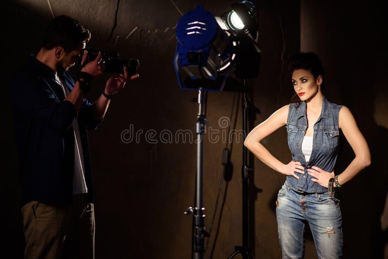 Ταλαντούχος νεαρός άνδρας που φωτογραφίζει το κορίτσι στο στούντιο στοκ φωτογραφία με δικαίωμα ελεύθερης χρήσης