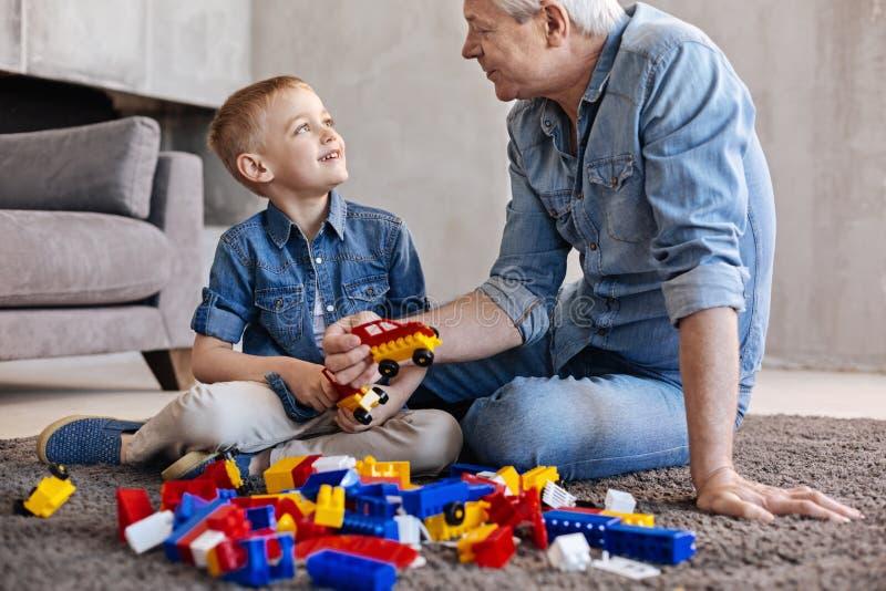 Ταλαντούχο παιδί και το grandpa του που χτίζουν κάτι από κοινού στοκ φωτογραφία με δικαίωμα ελεύθερης χρήσης