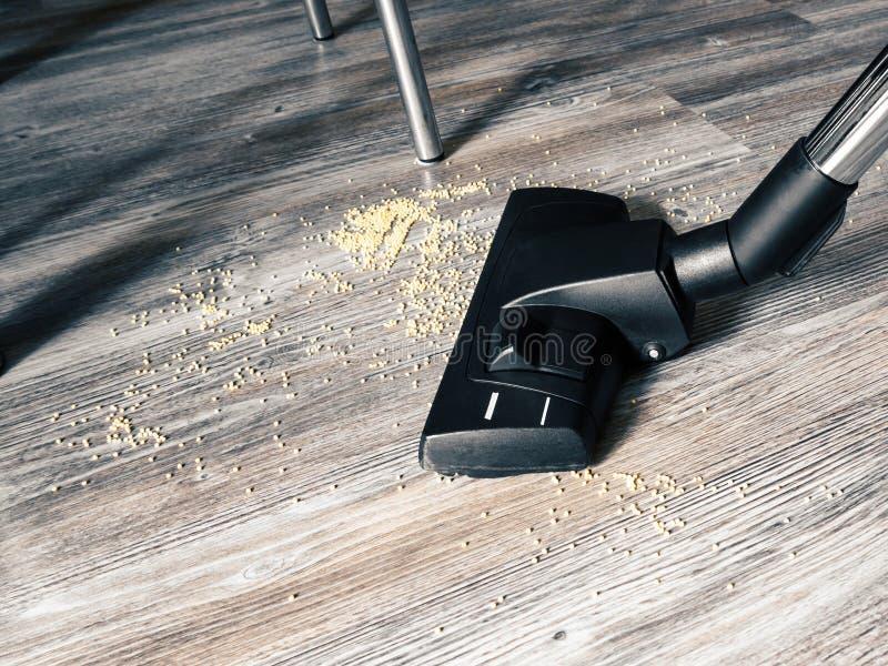 Τα απορρίματα στο πάτωμα καθαρίζονται με μια ηλεκτρική σκούπα Στο πλαίσιο, μια βούρτσα από μια ηλεκτρική σκούπα, πόδια των πινάκω στοκ εικόνα