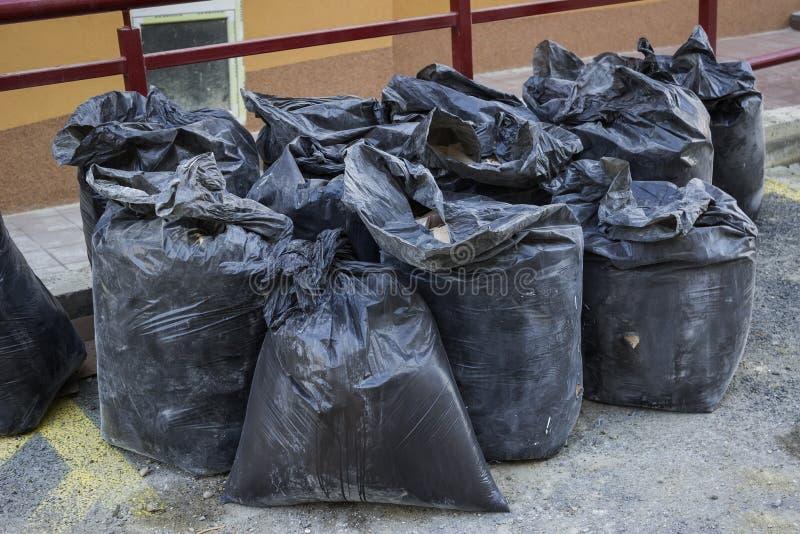Τα απόβλητα κατασκευής στους οικοδόμους σπαταλούν τις τσάντες στοκ εικόνα