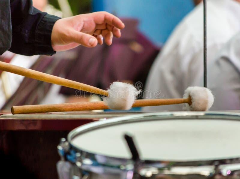 Τα αρσενικά ραβδιά withdrum χεριών τυμπανιστών μουσικών και παίζουν τύμπανο κοντά επάνω στοκ φωτογραφίες