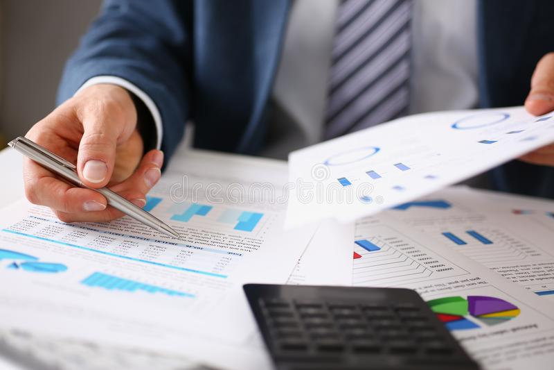 Τα αρσενικά χέρια κρατούν τα έγγραφα με τις οικονομικές στατιστικές στοκ εικόνα