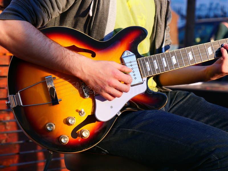 Τα αρσενικά χέρια παίζουν μια ηλεκτρική κιθάρα στοκ εικόνες με δικαίωμα ελεύθερης χρήσης
