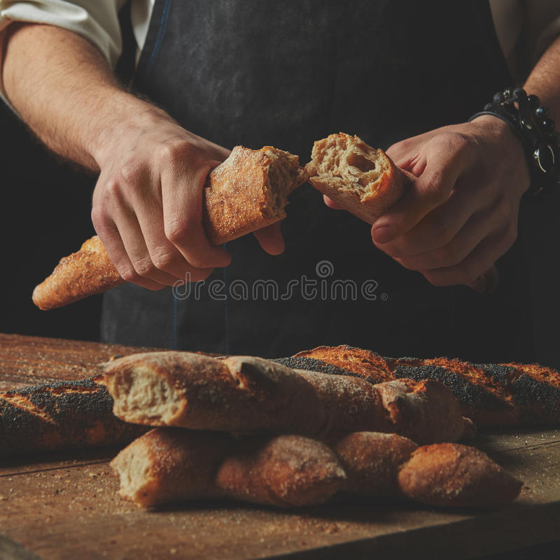 Τα αρσενικά χέρια σπάζουν το baguette στοκ φωτογραφίες με δικαίωμα ελεύθερης χρήσης