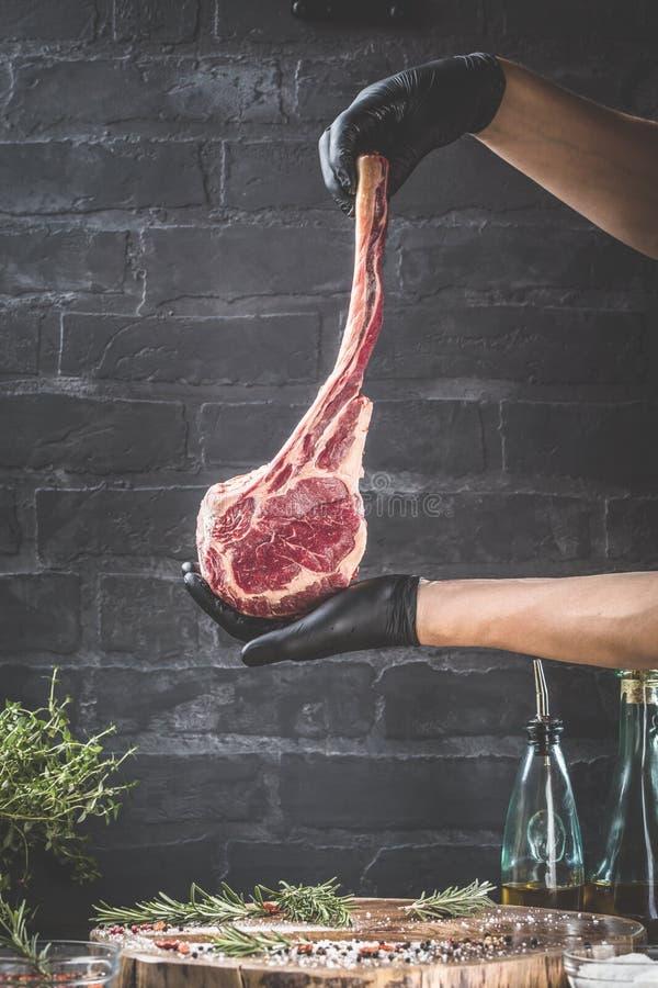Τα αρσενικά χέρια της μπριζόλας βόειου κρέατος τομαχόκ εκμετάλλευσης χασάπηδων ή μαγείρων στη σκοτεινή αγροτική κουζίνα παρουσιάζ στοκ φωτογραφίες με δικαίωμα ελεύθερης χρήσης