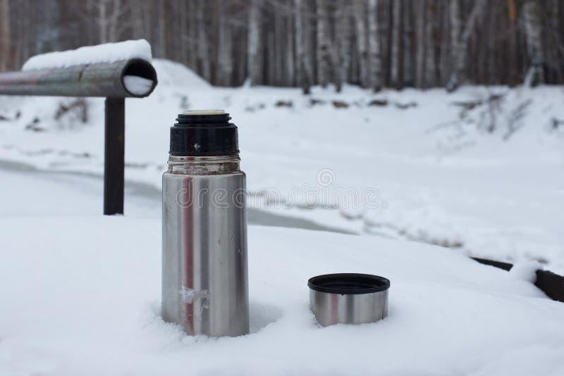 Τα ασημένια thermos με τον καφέ ή το τσάι είναι στο χιόνι στη χιονισμένη όχθη ποταμού υποβάθρου στοκ εικόνες με δικαίωμα ελεύθερης χρήσης