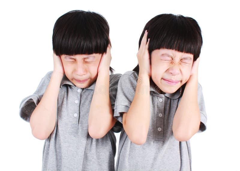 Τα ασιατικά αγόρια διδύμων καλύπτουν τα αυτιά τους που απομονώνονται στοκ φωτογραφία
