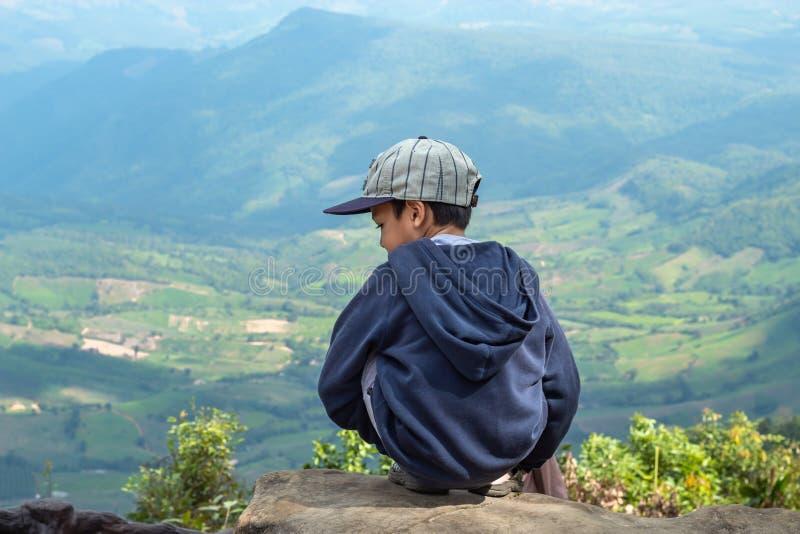 Τα ασιατικά αγόρια κάθονται στο βράχο βλέπουν τα βουνά και τον ουρανό στοκ φωτογραφία με δικαίωμα ελεύθερης χρήσης