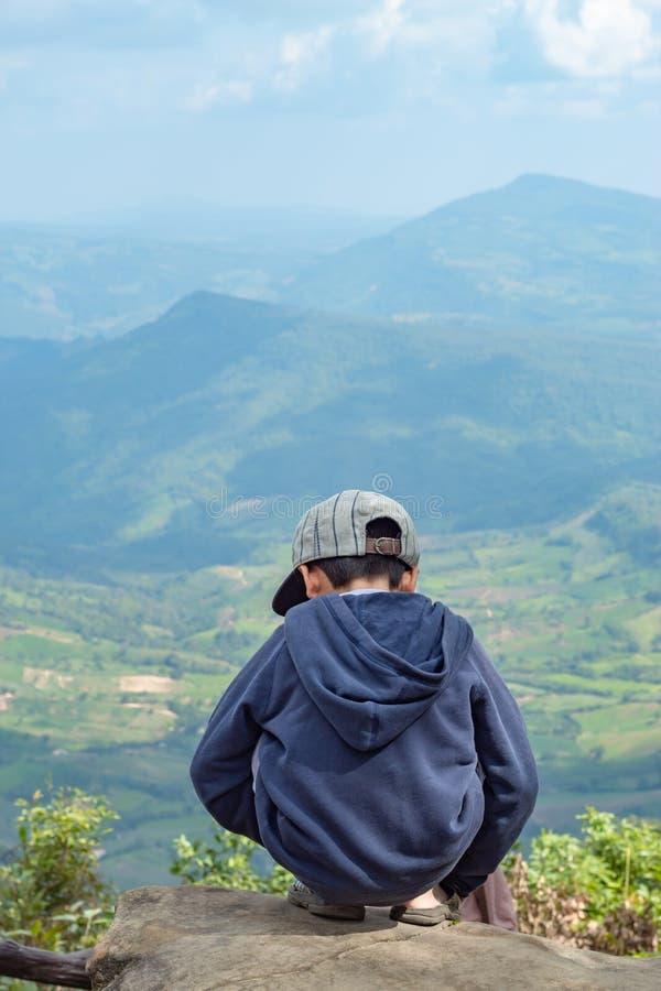 Τα ασιατικά αγόρια κάθονται στο βράχο βλέπουν τα βουνά και τον ουρανό στοκ εικόνα με δικαίωμα ελεύθερης χρήσης