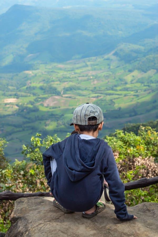 Τα ασιατικά αγόρια κάθονται στο βράχο βλέπουν τα βουνά και τον ουρανό στοκ εικόνες με δικαίωμα ελεύθερης χρήσης