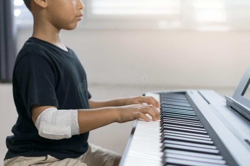 Τα ασιατικά αγόρια στα πληγωμένα χέρια παίζουν το πιάνο στοκ εικόνα με δικαίωμα ελεύθερης χρήσης