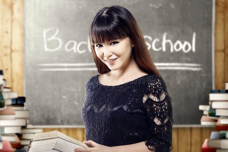 Τα ασιατικά βιβλία εκμετάλλευσης γυναικών σπουδαστών σε την παραδίδουν την τάξη με τους σωρούς των βιβλίων και του πίνακα στοκ εικόνα με δικαίωμα ελεύθερης χρήσης