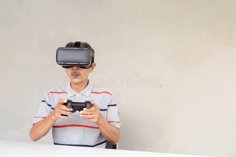 Τα ασιατικά ηλικιωμένα άτομα απολαμβάνουν τη σύγχρονη τεχνολογία Παιχνίδι online παιχνιδιού μέσω των γυαλιών εικονικής πραγματικό στοκ φωτογραφία