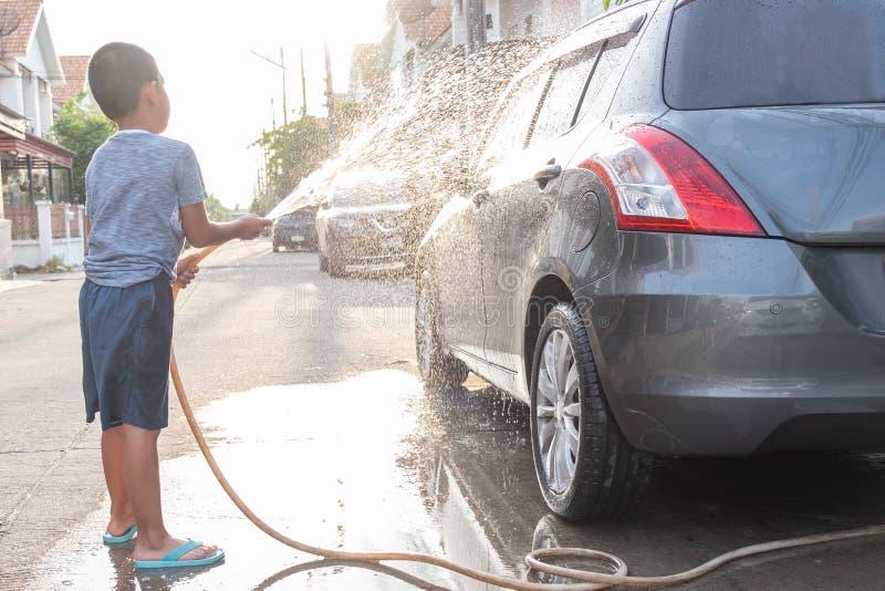 Τα ασιατικά παιδιά χρησιμοποιούν τη μάνικα νερού στο αυτοκίνητο πλύσης στοκ φωτογραφίες με δικαίωμα ελεύθερης χρήσης