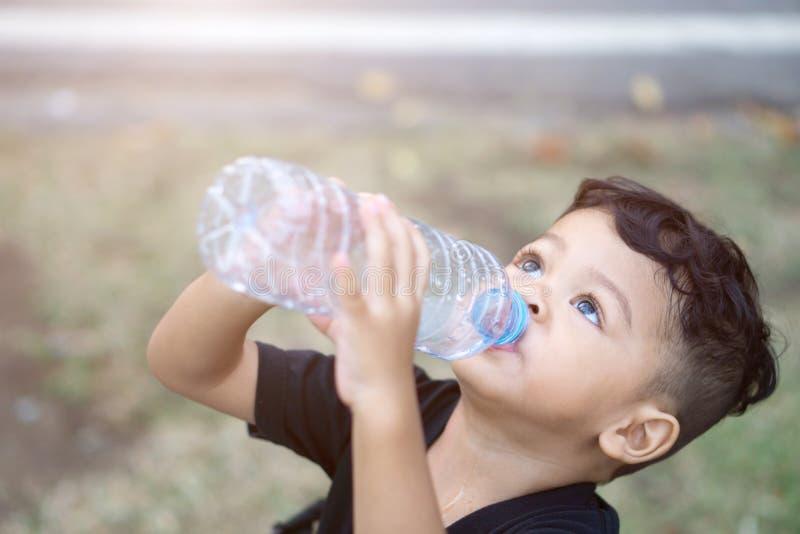 Τα ασιατικά ταϊλανδικά παιδιά πίνουν το νερό στο πάρκο στοκ εικόνα με δικαίωμα ελεύθερης χρήσης