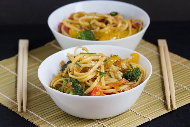 Τα ασιατικά τρόφιμα, δύο κύπελλα ανακατώνουν τα νουντλς τηγανητών με τα λαχανικά και τη σάλτσα σόγιας σε ένα χαλί μπαμπού, μαύρο  στοκ εικόνες