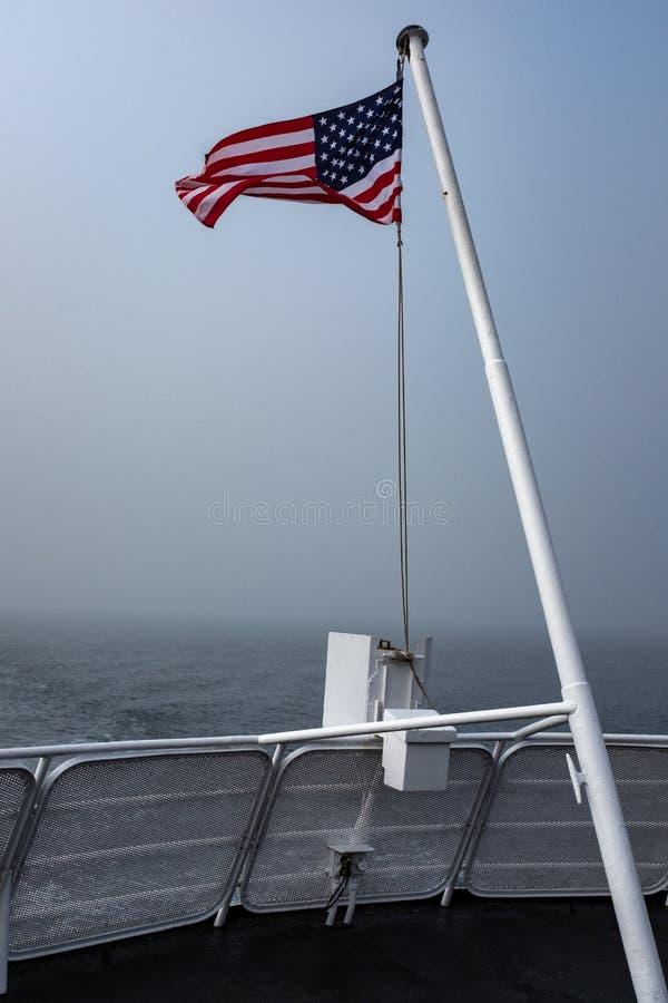 Τα αστέρια και τα λωρίδες που κυματίζουν στην κορυφή ενός πόλου σημαιών στον αέρα στο πίσω μέρος ενός περάσματος πορθμείων στον Κ στοκ εικόνα