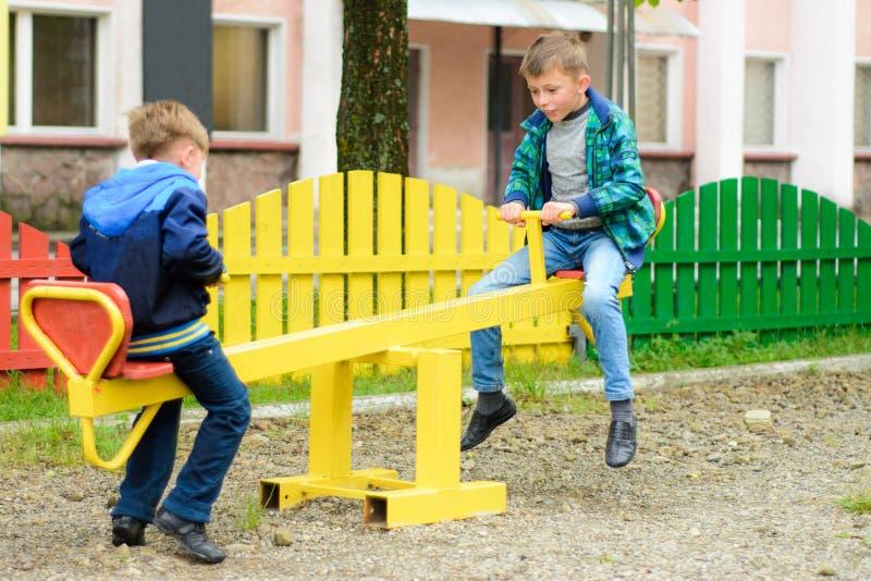 Τα αστεία αγόρια ταλαντεύονται σε έναν κίτρινο ταλάντευση-πίνακα στοκ φωτογραφίες