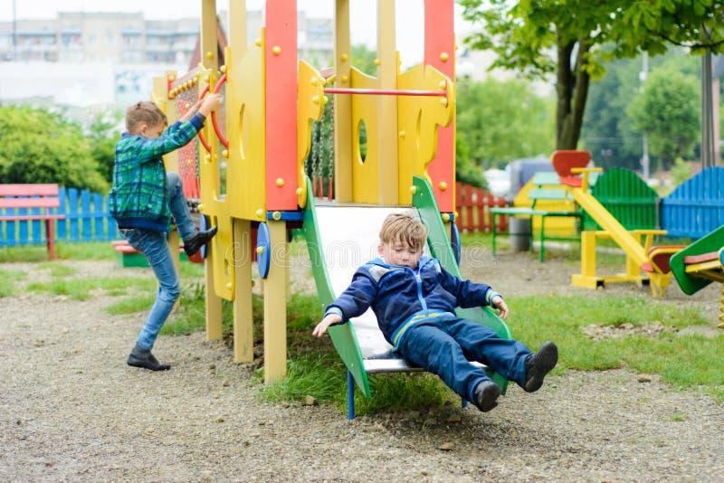 Τα αστεία παιδιά παίζουν σε μια παιδική χαρά παιδιών ` s στοκ εικόνες