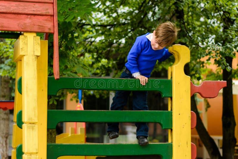 Τα αστεία παιδιά παίζουν σε μια παιδική χαρά παιδιών ` s στοκ εικόνα