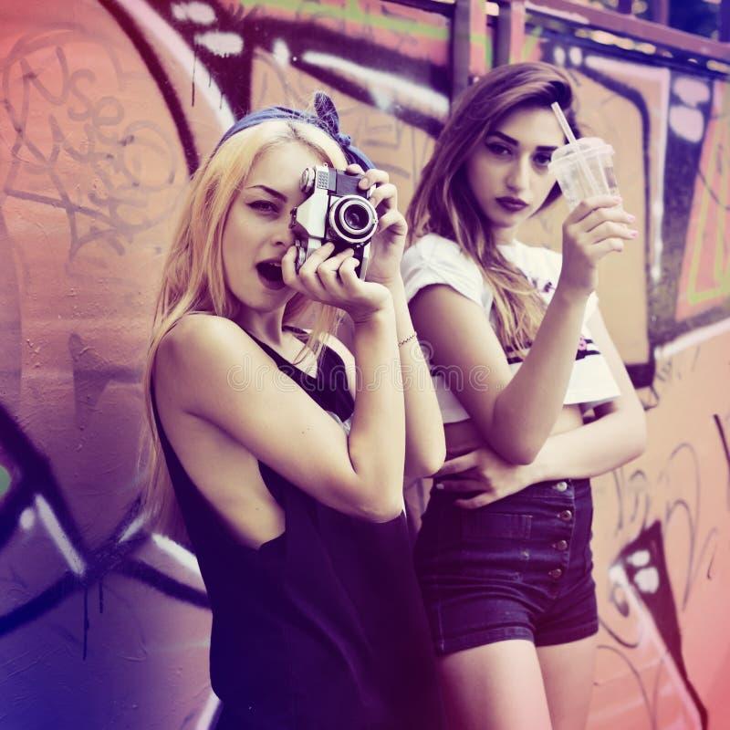 Τα αστικά κορίτσια έχουν τη διασκέδαση με την αναδρομική εκλεκτής ποιότητας κάμερα φωτογραφιών υπαίθρια στοκ εικόνα