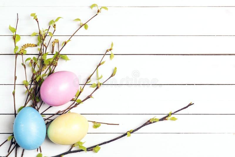 Τα αυγά Πάσχας με τη σημύδα διακλαδίζονται με τα πρώτα φύλλα σε ένα άσπρο ξύλινο υπόβαθρο στοκ εικόνες με δικαίωμα ελεύθερης χρήσης