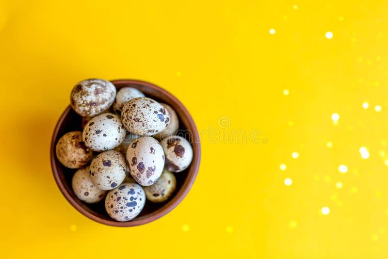 Τα αυγά Πάσχας ορτυκιών σε ένα ξύλινο πιάτο σε ένα κίτρινο υπόβαθρο με ακτινοβολούν στοκ φωτογραφία με δικαίωμα ελεύθερης χρήσης