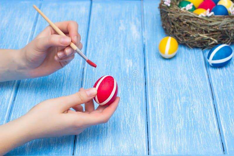Τα αυγά Πάσχας χρωμάτων κοριτσιών με μια βούρτσα και ένα χρώμα σε ένα ξύλινο υπόβαθρο στο οποίο βρίσκεται μια φωλιά με τα ζωηρόχρ στοκ εικόνες