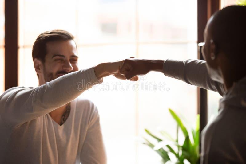 Τα αφρικανικά και καυκάσια άτομα που χαιρετούν το ένα το άλλο κάνουν την πρόσκρουση πυγμών στοκ φωτογραφία με δικαίωμα ελεύθερης χρήσης